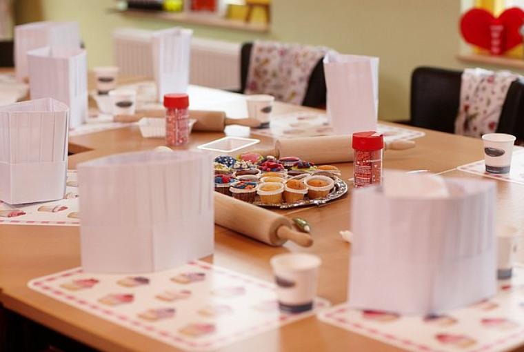 Gedekte_tafel_met_cupcakes_koksmuts_schortjes_in_animatieruimte_voor_kinderfeestje_Preston_Palace